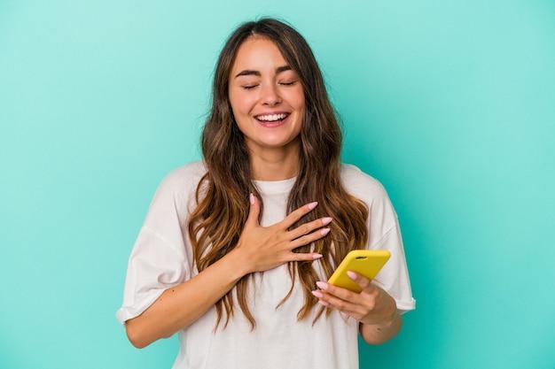 Jeune femme de race blanche tenant un téléphone portable isolé sur fond bleu rit fort en gardant la main sur la poitrine.