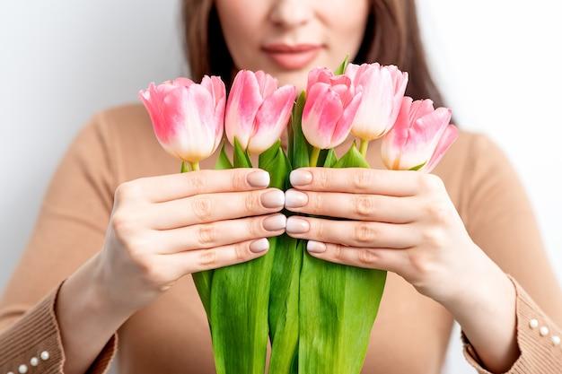 Une jeune femme de race blanche tient des tulipes roses dans ses mains sur un fond blanc
