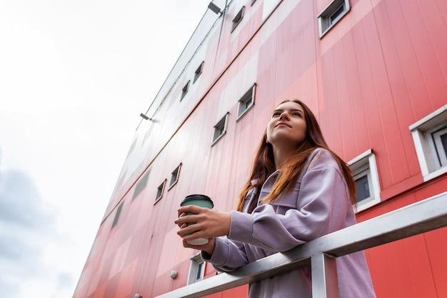 Jeune femme de race blanche avec un verre de café