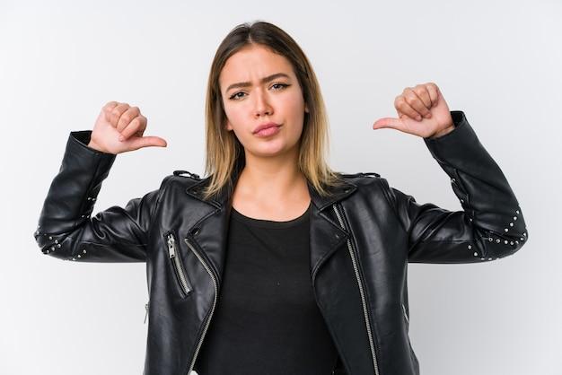 Jeune femme de race blanche vêtue d'une veste en cuir noir se sent fière et confiante, exemple à suivre.
