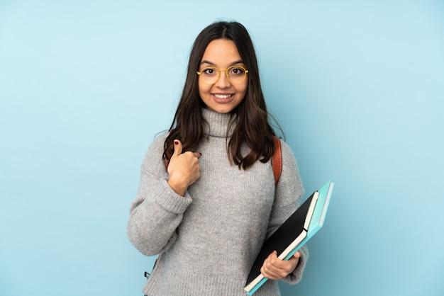 Jeune femme de race mixte aller à l'école isolé sur mur bleu avec une expression faciale surprise