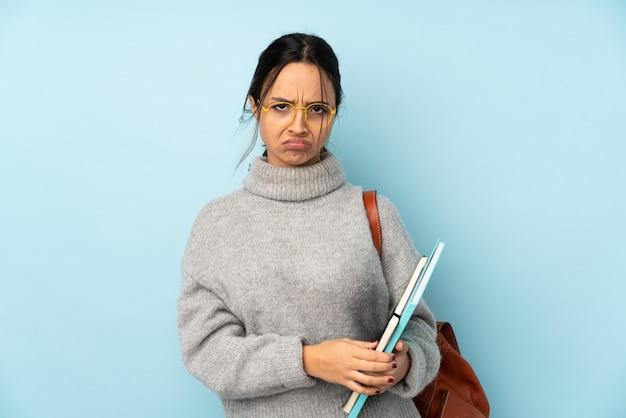 Jeune femme de race mixte aller à l'école sur le mur bleu se sentir bouleversé