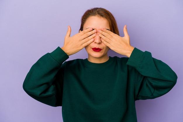 Jeune femme de race mixte arabe peur couvrant les yeux avec les mains.