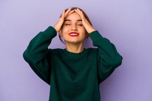 Jeune femme de race mixte arabe rit joyeusement en gardant les mains sur la tête. concept de bonheur.
