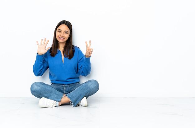 Jeune femme de race mixte assis sur le sol isolé sur fond blanc en comptant sept avec les doigts