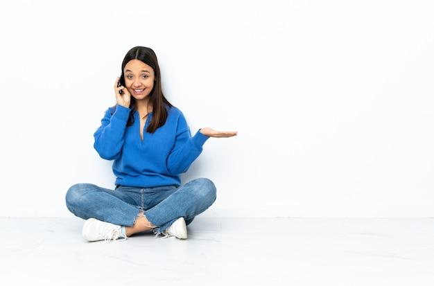Jeune femme de race mixte assis sur le sol sur le mur blanc en gardant une conversation avec le téléphone mobile avec quelqu'un