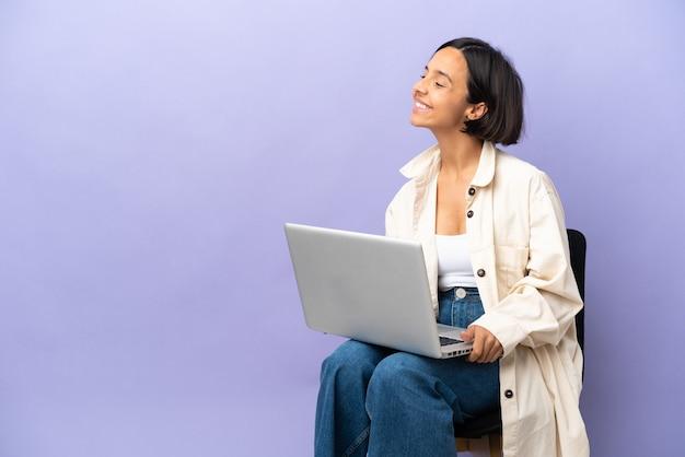 Jeune femme de race mixte assise sur une chaise avec un ordinateur portable isolé sur fond violet à côté