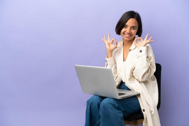 Jeune femme de race mixte assise sur une chaise avec un ordinateur portable isolé montrant un signe ok à deux mains