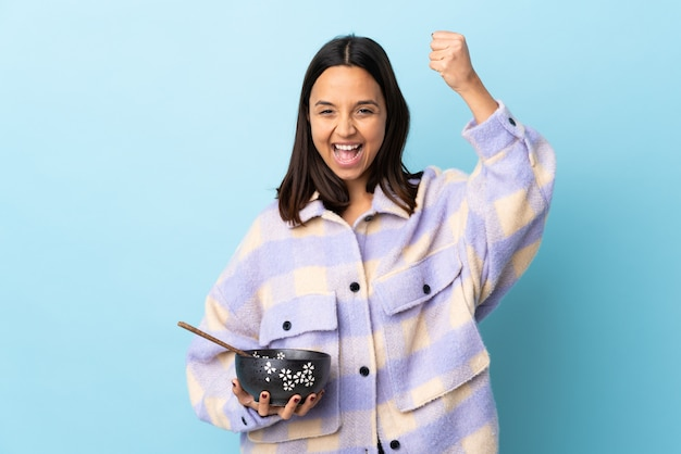 Jeune femme de race mixte brune tenant un bol plein de nouilles sur fond bleu isolé célébrant une victoire