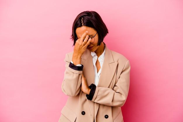 Jeune femme de race mixte isolée sur fond rose ayant un mal de tête, touchant le devant du visage.