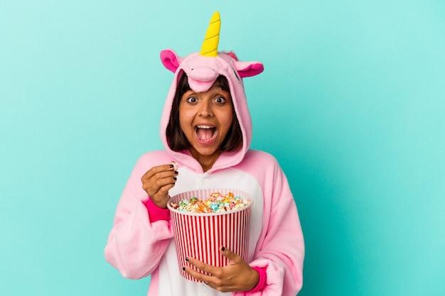 Jeune femme de race mixte portant un pyjama de licorne mangeant du maïs soufflé