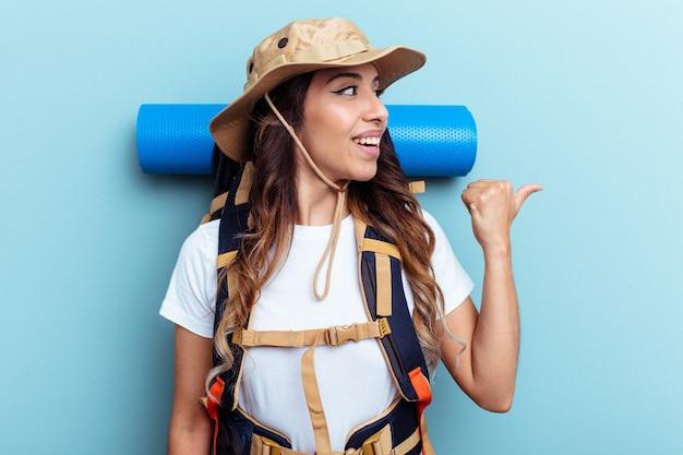 Jeune femme de race mixte de randonneur isolée sur des points de fond bleu avec le pouce loin, riant et insouciant.