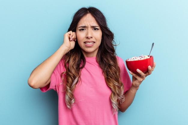 Jeune femme de race mixte tenant un bol de céréales isolé sur fond bleu couvrant les oreilles avec les mains.