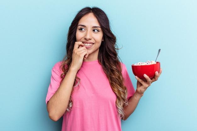 Jeune femme de race mixte tenant un bol de céréales isolé sur fond bleu détendue en pensant à quelque chose en regardant un espace de copie.