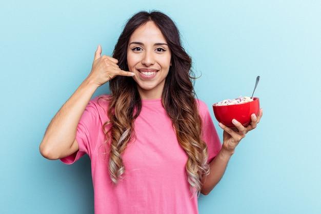 Jeune femme de race mixte tenant un bol de céréales isolé sur fond bleu montrant un geste d'appel de téléphone portable avec les doigts.