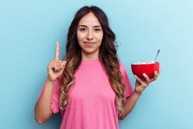 Jeune femme de race mixte tenant un bol de céréales isolé sur fond bleu montrant le numéro un avec le doigt.