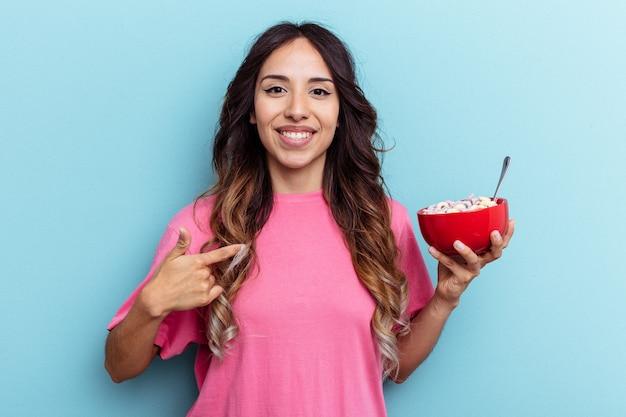 Jeune femme de race mixte tenant un bol de céréales isolé sur fond bleu personne pointant à la main vers un espace de copie de chemise, fier et confiant