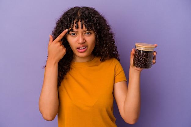 Jeune femme de race mixte tenant une bouteille de grains de café isolée sur fond violet montrant un geste de déception avec l'index.