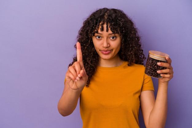 Jeune femme de race mixte tenant une bouteille de grains de café isolée sur fond violet montrant le numéro un avec le doigt.