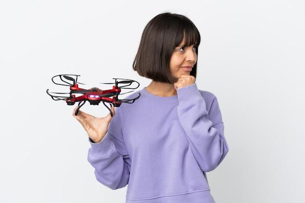 Jeune femme de race mixte tenant un drone isolé sur fond blanc ayant des doutes