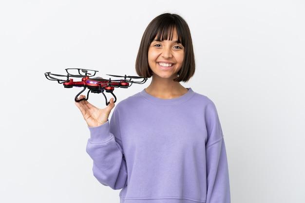 Jeune femme de race mixte tenant un drone isolé sur fond blanc à côté