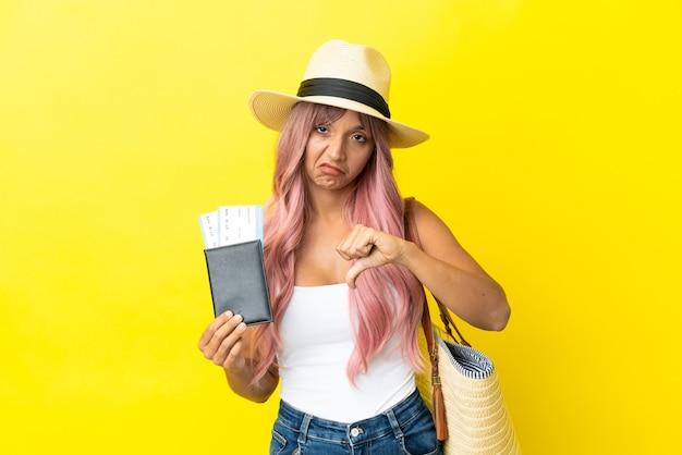 Jeune femme de race mixte tenant un passeport et un sac de plage isolé sur fond jaune montrant le pouce vers le bas avec une expression négative