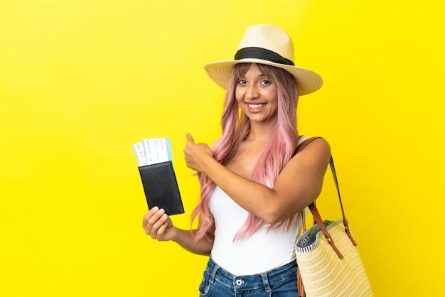 Jeune femme de race mixte tenant un passeport et un sac de plage isolé sur fond jaune pointant vers l'arrière