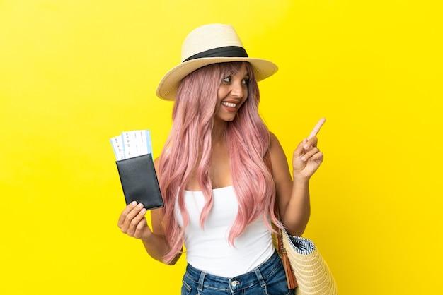 Jeune femme de race mixte tenant un passeport et un sac de plage isolé sur fond jaune pointant vers une excellente idée