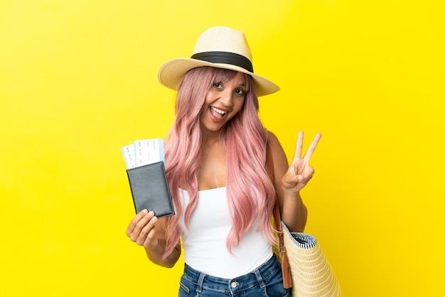 Jeune femme de race mixte tenant un passeport et un sac de plage isolé sur fond jaune souriant et montrant le signe de la victoire