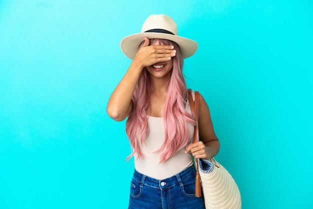 Jeune femme de race mixte tenant un sac de plage avec pamela isolé sur fond bleu couvrant les yeux par les mains
