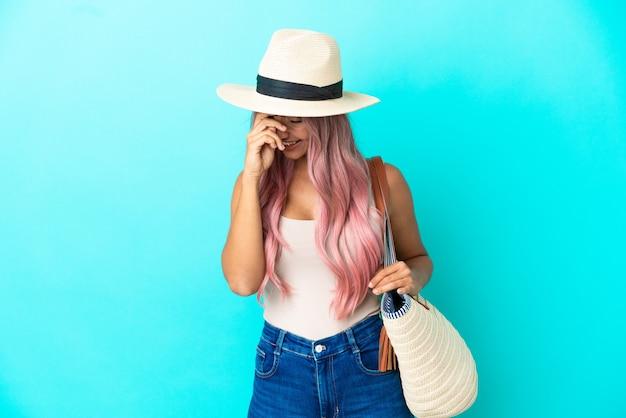 Jeune femme de race mixte tenant un sac de plage avec pamela isolé sur fond bleu en riant