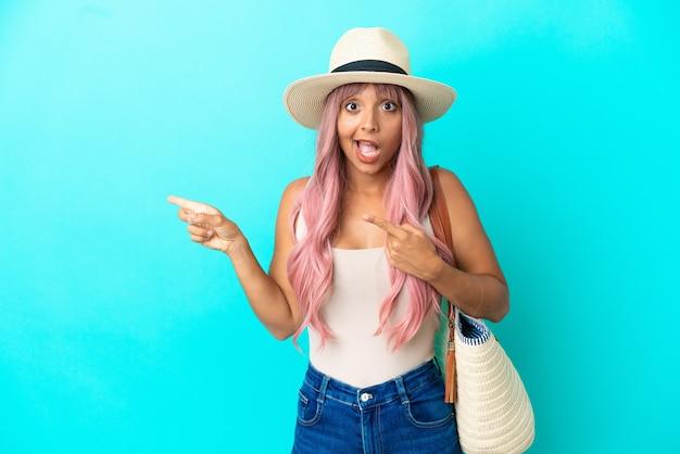 Jeune femme de race mixte tenant un sac de plage avec pamela isolé sur fond bleu surpris et pointant du côté