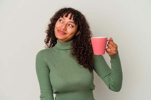 Jeune femme de race mixte tenant une tasse isolée sur fond blanc rêvant d'atteindre des objectifs et des buts