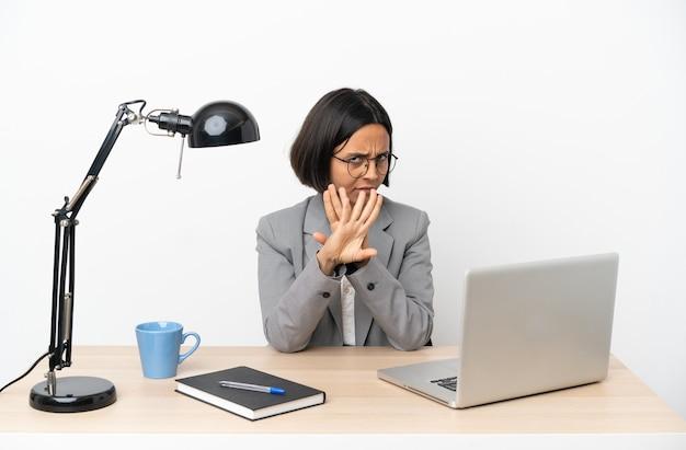 Jeune femme de race mixte travaillant au bureau faisant un geste d'arrêt avec sa main pour arrêter un acte