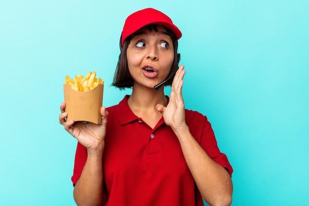 Jeune femme de race mixte travailleur de restauration rapide tenant des frites isolées sur fond bleu dit une nouvelle secrète de freinage à chaud et regarde de côté