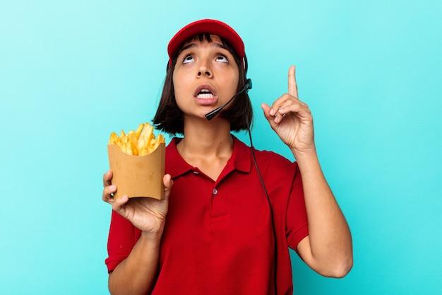 Jeune femme de race mixte travailleur de restauration rapide tenant des frites isolées sur fond bleu pointant vers le haut avec la bouche ouverte.