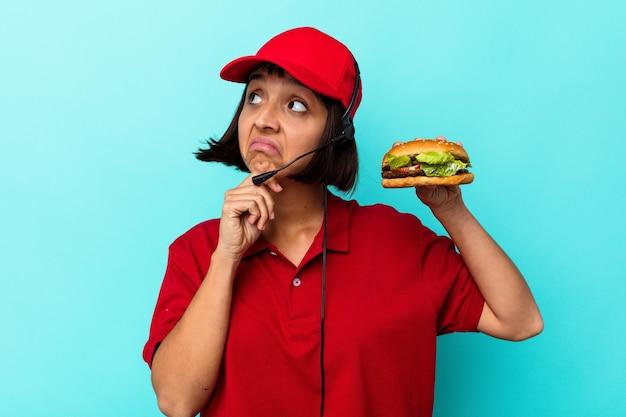 Jeune femme de race mixte travailleur de restauration rapide tenant un hamburger isolé sur fond bleu
