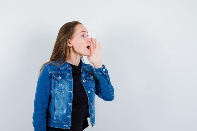 Jeune femme racontant le secret avec la main près de la bouche en blouse, vue de face.