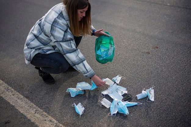 Jeune femme ramassant des masques sales du sol.