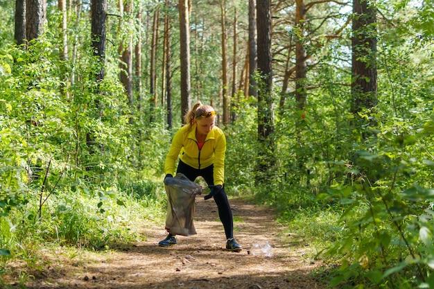 Une jeune femme ramasse des déchets dans un sac poubelle en faisant du jogging dans un parc