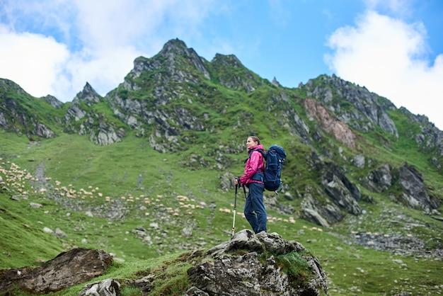 Jeune femme randonneuse bénéficiant d'une belle journée ensoleillée dans les montagnes au repos en regardant autour