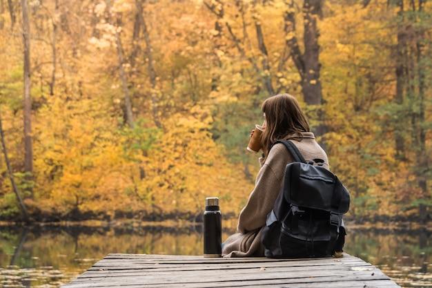 Jeune femme randonneuse avec sac à dos se trouve au bord de la rivière, boit du café et regarde de beaux paysages d'été indien