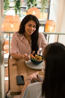 Jeune femme ravie regardant son amie avec un sourire tout en tenant une fourchette pendant le déjeuner dans un café