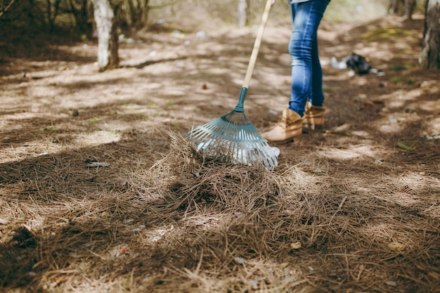 Jeune femme recadrée en vêtements décontractés nettoyant les ordures à l'aide d'un râteau pour la collecte des ordures dans un parc jonché. problème de pollution de l'environnement. arrêtez les ordures de la nature, concept de protection de l'environnement.