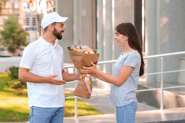 Jeune femme, réception, bouquet fleurs, de, courrier, dehors