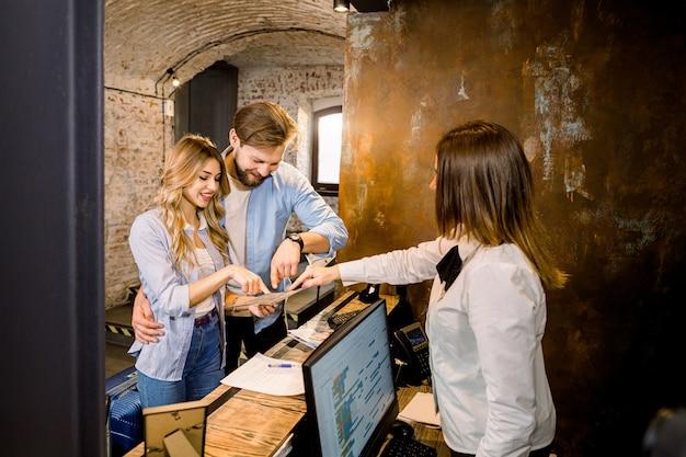Jeune femme réceptionniste donnant des informations sur le plan de la ville à un jeune couple caucasien, homme et femme.