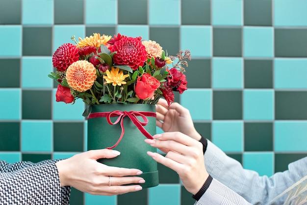 Jeune femme recevant de belles fleurs de pivoine de la femme de livraison.