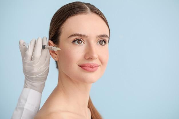 Jeune femme recevant une injection de remplissage contre la surface de couleur
