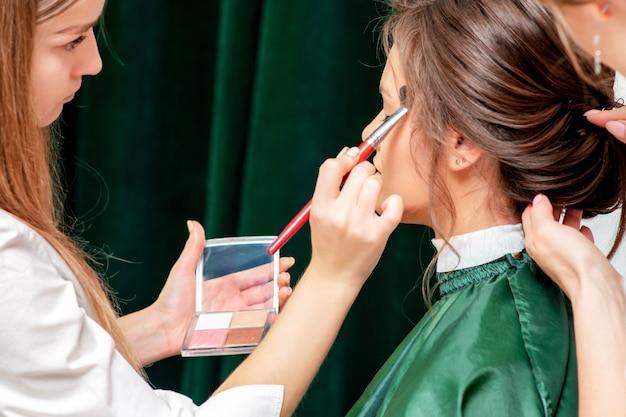 Jeune femme recevant le maquillage et la coiffure par un maquilleur professionnel et un coiffeur dans un salon de beauté.