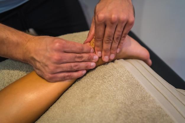 Une jeune femme recevant un massage aux jambes par un physiothérapeute. physio, ostéopathie